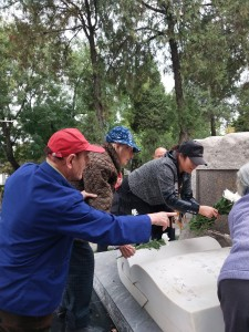 Isabel Crook laying a flower on Israel Epstein's grave